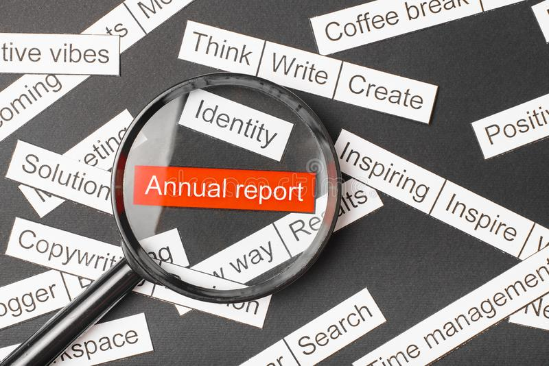 Magnifier glass over the red inscription annual report cut out of paper. Surrounded by other inscriptions on a dark background. Word cloud concept royalty free stock photography