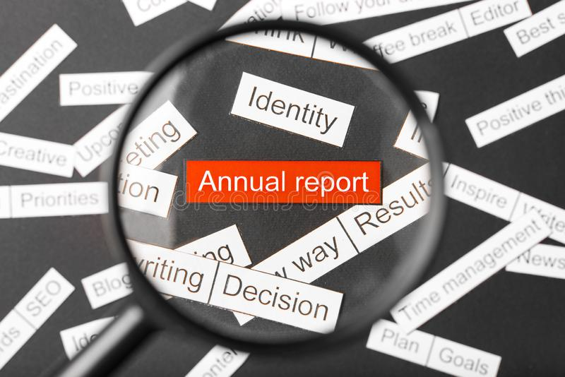 Magnifier glass over the red inscription annual report cut out of paper. Surrounded by other inscriptions on a dark background. Word cloud concept royalty free stock photo
