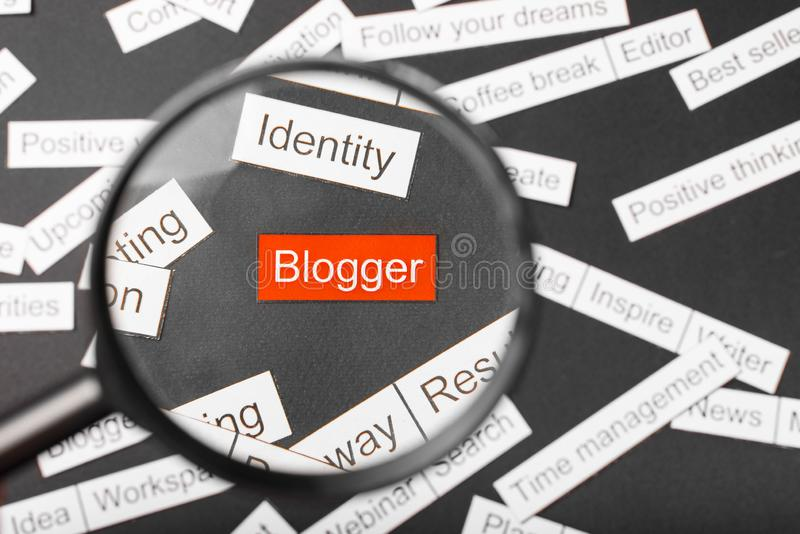 Magnifier glass over the red inscription blogger cut out of paper. Surrounded by other inscriptions on a dark background. Word. Cloud concept stock photography
