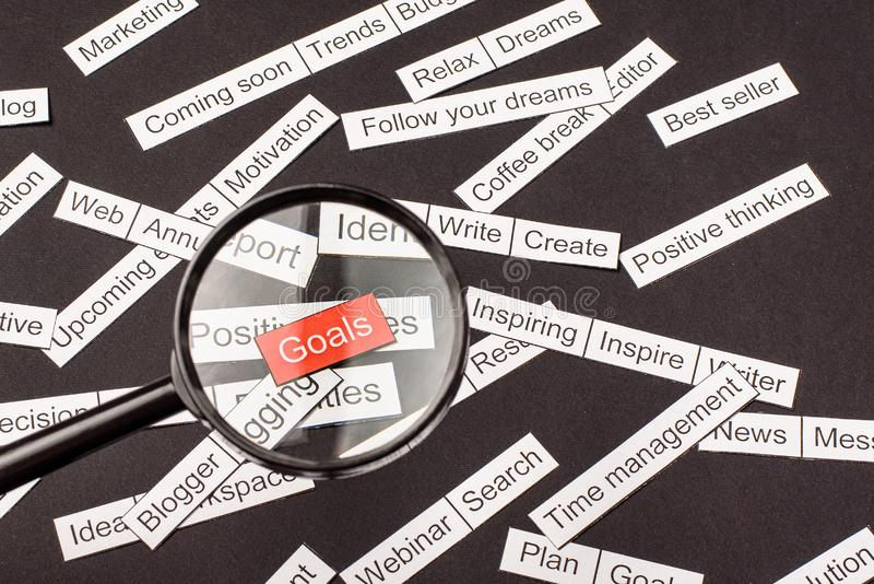 Magnifier glass over the red inscription Goals cut out of paper. Surrounded by other inscriptions on a dark background. Word cloud. Concept stock photo