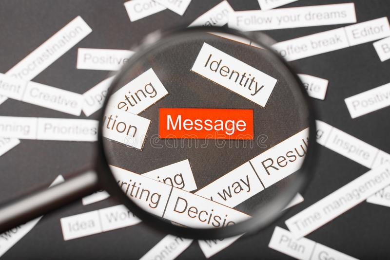 Magnifier glass over the red inscription message cut out of paper. Surrounded by other inscriptions on a dark background. Word. Cloud concept stock photos