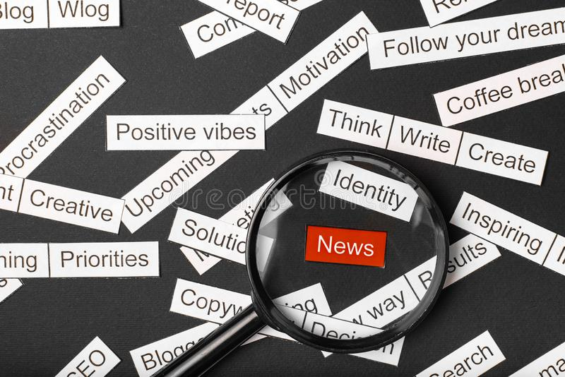 Magnifier glass over the red inscription news cut out of paper. Surrounded by other inscriptions on a dark background. Word cloud. Concept stock photography