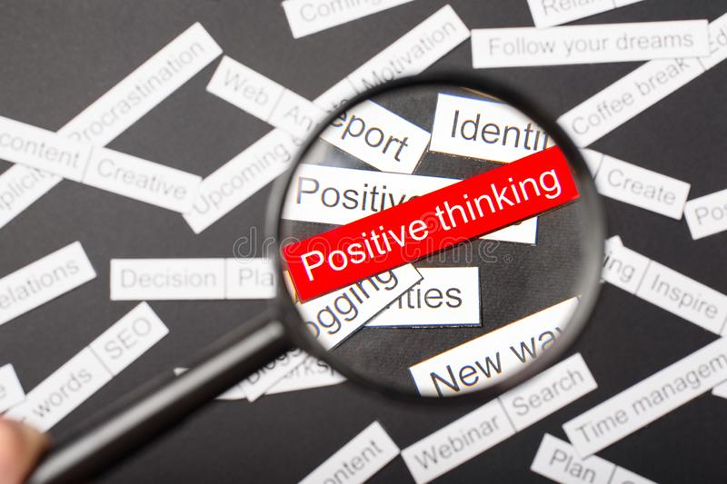 Magnifier glass over the red inscription Positive thinking cut out of paper. Surrounded by other inscriptions on a dark background. Word cloud concept stock image