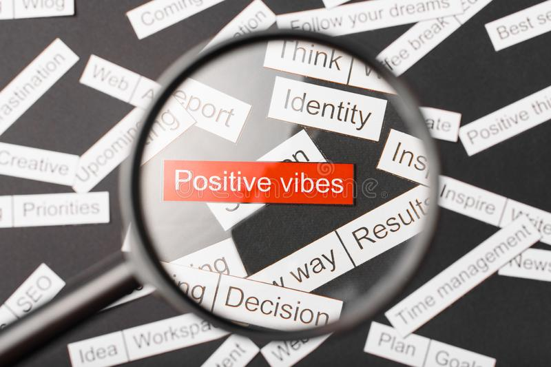 Magnifier glass over the red inscription positive vibes cut out of paper. Surrounded by other inscriptions on a dark background. Word cloud concept royalty free stock images