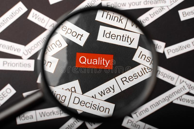 Magnifier glass over the red inscription quality cut out of paper. Surrounded by other inscriptions on a dark background. Word. Cloud concept royalty free stock image