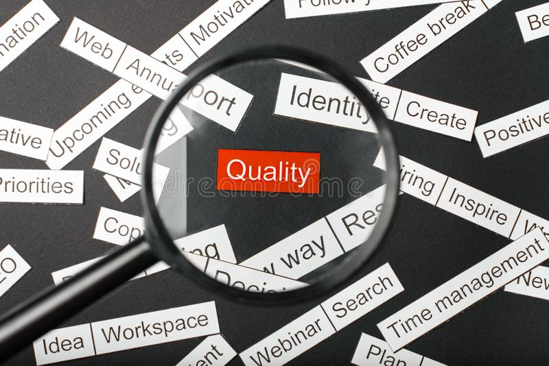 Magnifier glass over the red inscription quality cut out of paper. Surrounded by other inscriptions on a dark background. Word. Cloud concept royalty free stock photo
