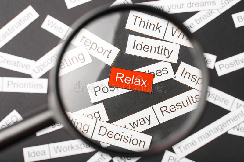 Magnifier glass over the red inscription relax cut out of paper. Surrounded by other inscriptions on a dark background. Word cloud. Concept stock images