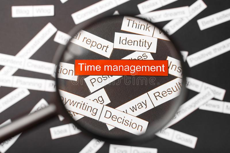 Magnifier glass over the red inscription time management cut out of paper. Surrounded by other inscriptions on a dark background. Word cloud concept stock photos