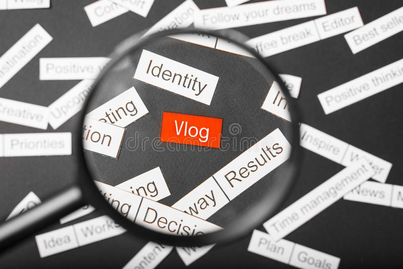 Magnifier glass over the red inscription vlog cut out of paper. Surrounded by other inscriptions on a dark background. Word cloud.  royalty free stock images