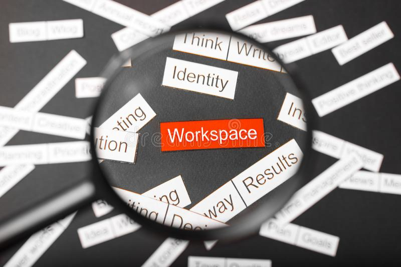 Magnifier glass over the red inscription workspace cut out of paper. Surrounded by other inscriptions on a dark background. Word. Cloud concept royalty free stock photos