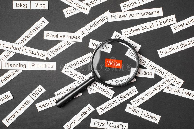 Magnifier glass over the red inscription write cut out of paper. Surrounded by other inscriptions on a dark background. Word cloud. Concept stock photography