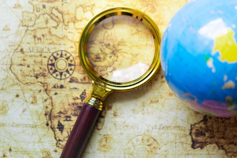 Magnifier and globe on old map background. royalty free stock photography