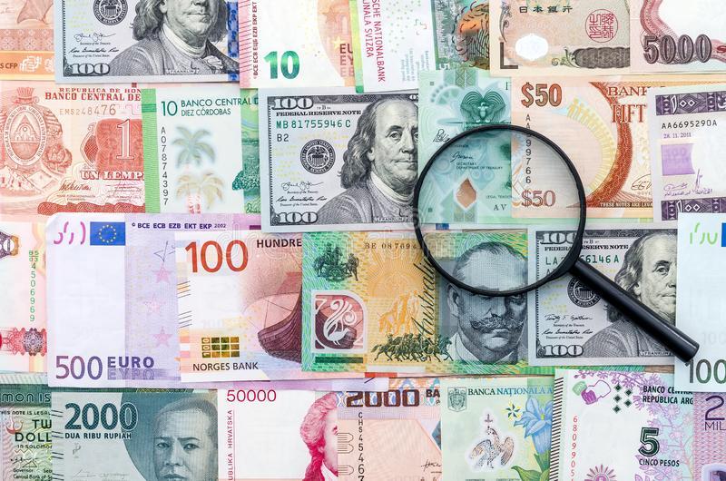 Magnifier on international money banknotes background, close up royalty free stock images