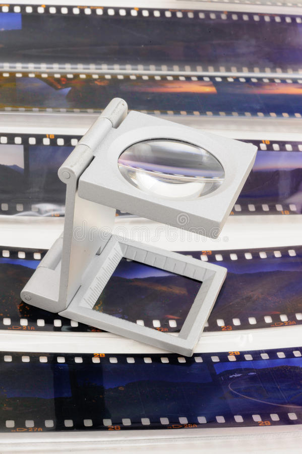 Magnifier loupe over transparency film slide. Magnifier loupe over transparency film slide for editerial department royalty free stock images