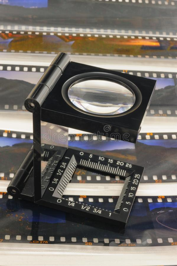 Magnifier loupe over transparency film. Magnifier loupe over transparency film slide for editerial department stock photography
