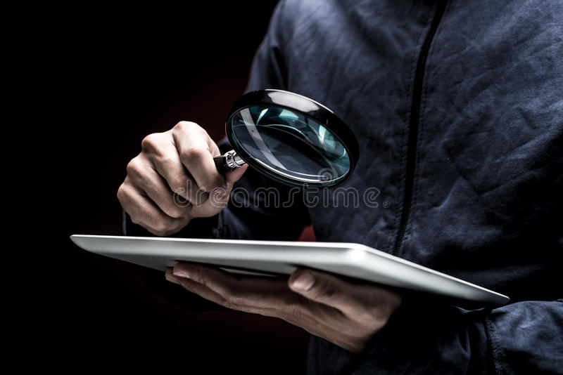 Magnifier. Man looking at the screen of a digital tablet with a magnifier stock image