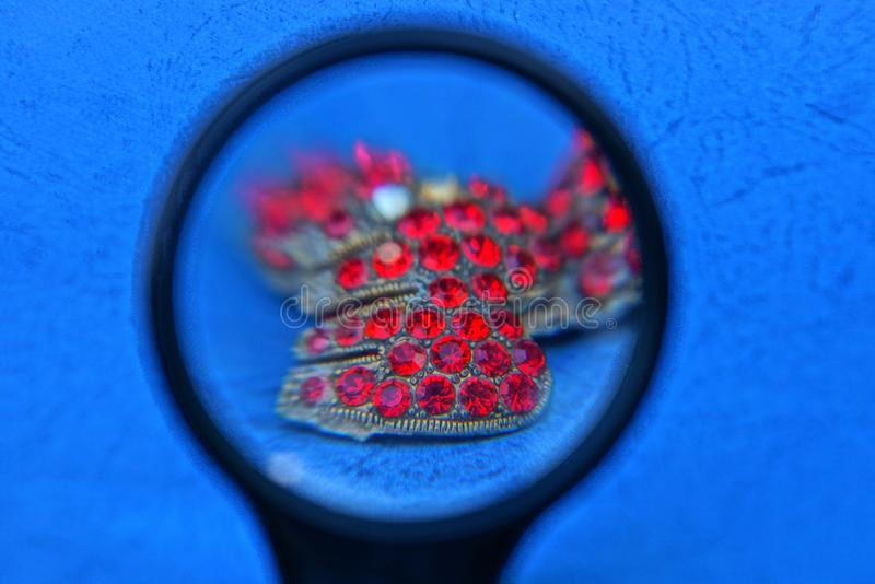 Magnifier and old golden jewelery with small red rubies on the blue table stock photography