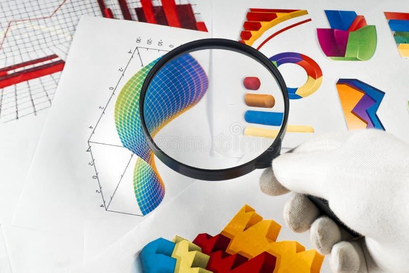 Magnifier op de achtergrond van grafische grafieken stock afbeelding