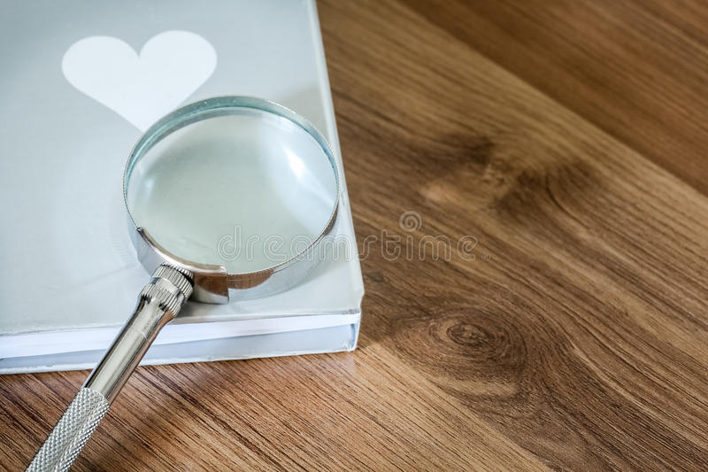 Magnifier over the book on the wooden table with copy space royalty free stock image