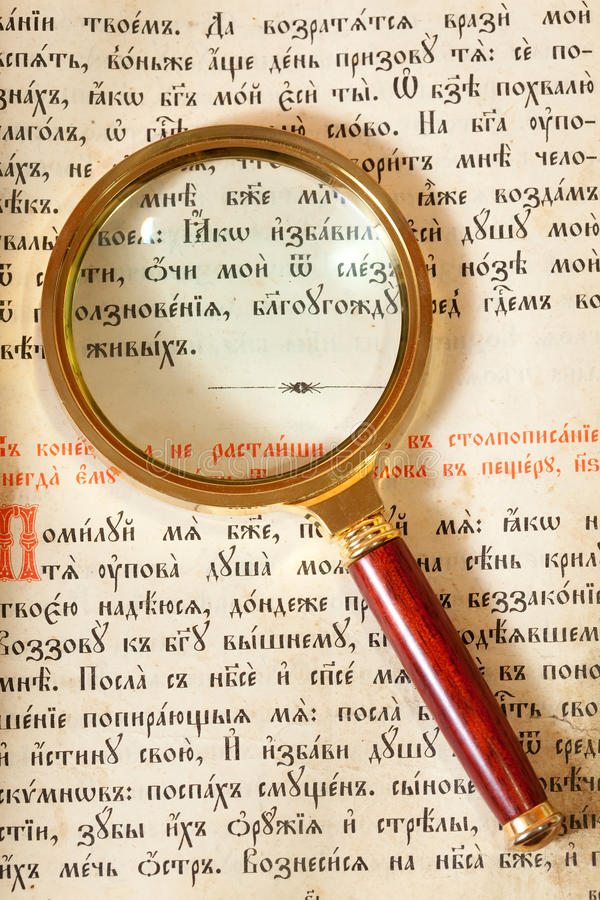 Magnifier on page of old book stock photography