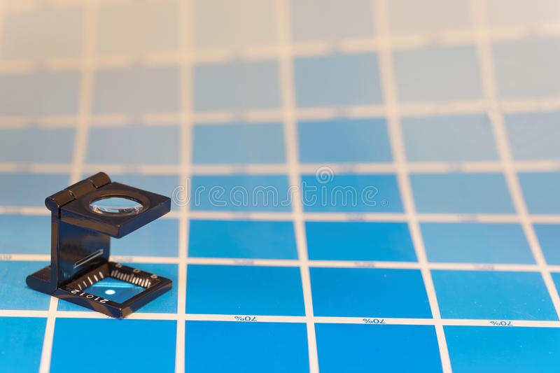 Magnifier or printer`s loupe sits on a cyan test sheet stock image