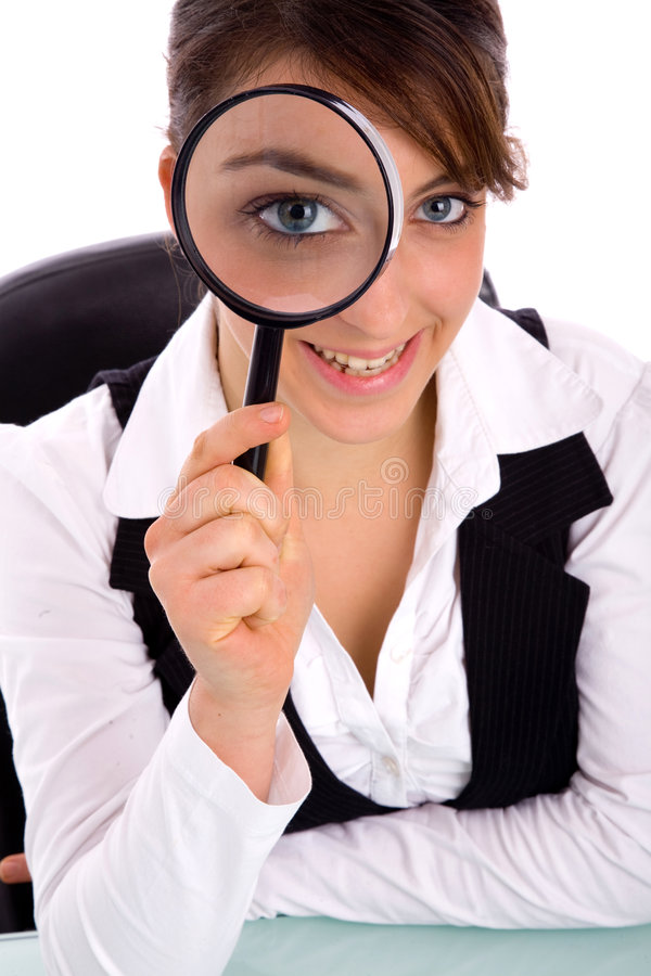 Magnifier sorridente della holding della giovane donna fotografia stock