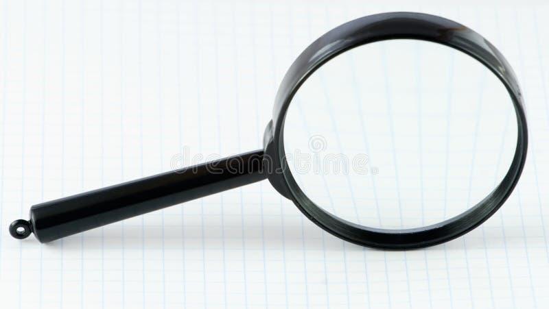 Magnifier su un documento di per la matematica immagini stock