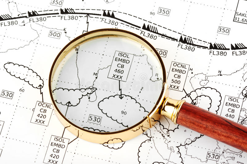 Magnifier with weather map. Closeup Magnifier with aviation weather map royalty free stock photos