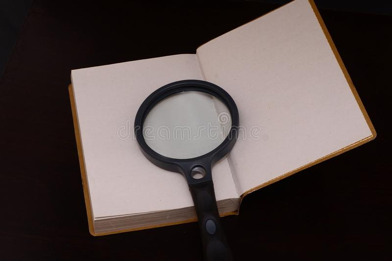 Magnifing glass on a book to help facilitate the vision for reading and to educate royalty free stock photos