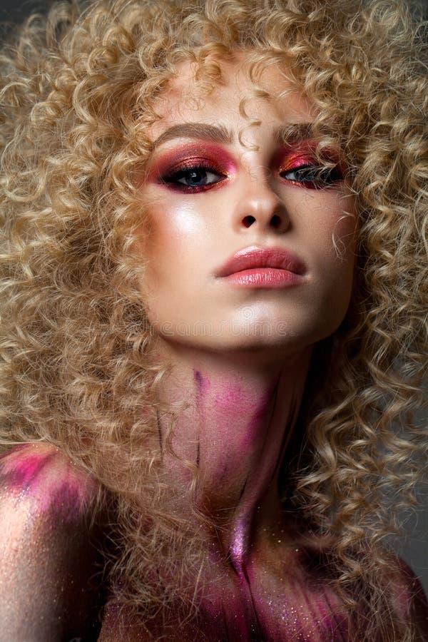 Magnifique modèle blond avec une coiffure très volumineuse, des yeux colorés rouges fumés et des éléments d'art corporel photographie stock libre de droits