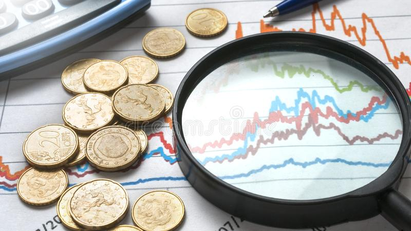A magnifiyng glass over a financial graph with some euro coins, a pen and a calculator stock images
