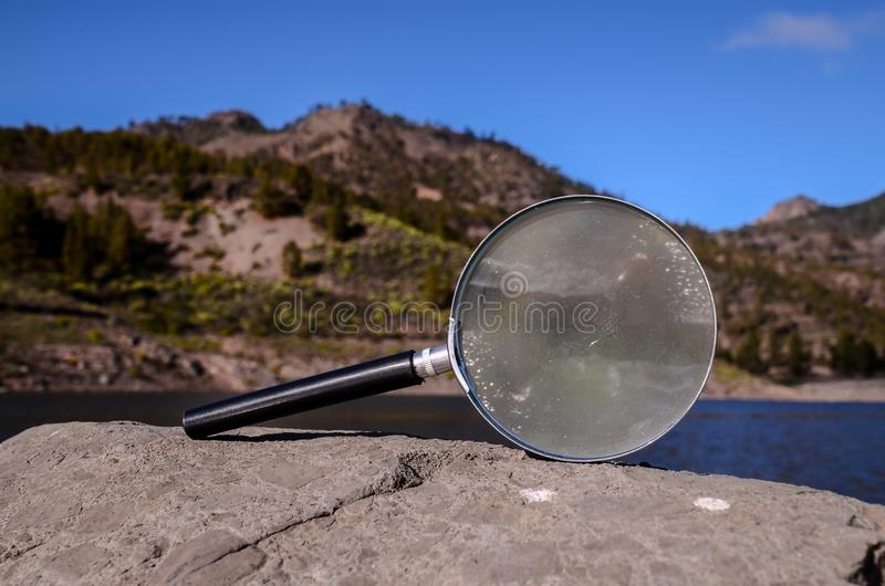 Magnify Glass Loupe on the Volcanic Rock. Investigation Concept Magnify Glass Loupe on the Volcanic Rock near a lake stock images