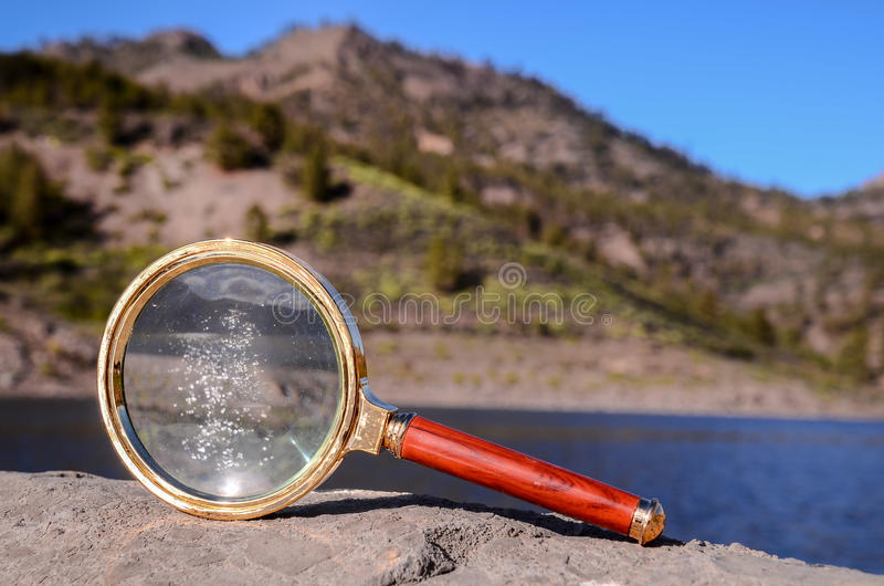 Magnify Glass Loupe on the Volcanic Rock. Investigation Concept Magnify Glass Loupe on the Volcanic Rock near a lake royalty free stock photos