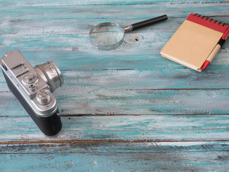 Magnify Glass, notepad and vintage camera blue background. Magnify Glass, notepad and vintage camera blue wooden background royalty free stock photography