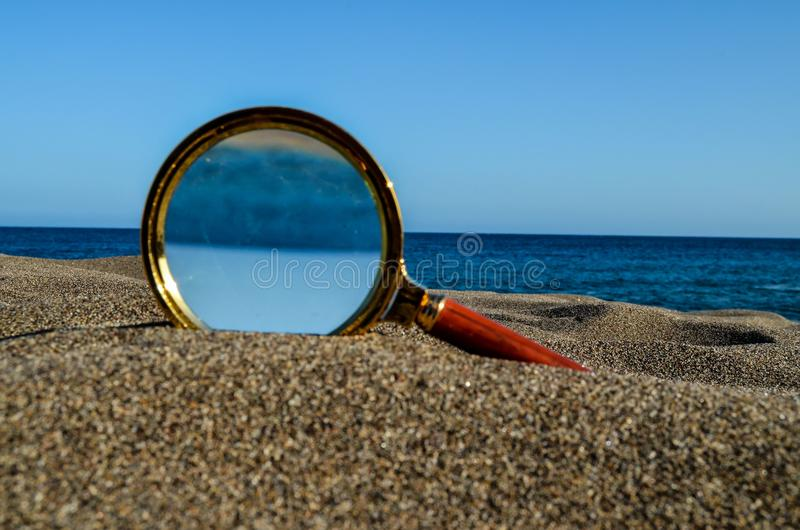 Magnify Glass on the Sand Beach. Photo Picture of a Loupe Magnify Glass on the Sand Beach stock photography