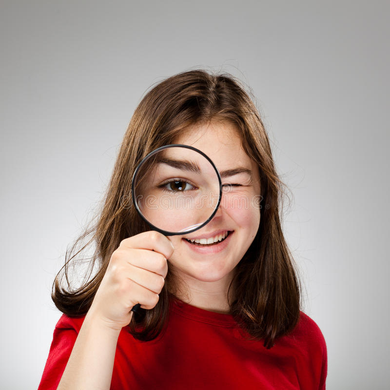 Magnifying glass. Young girl holding magnifying glass on gray background royalty free stock photos