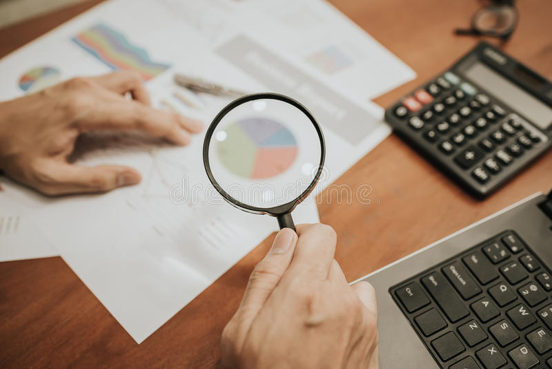 Magnifying glass analyzing business financial data. royalty free stock photography