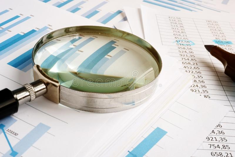 Magnifying glass for audit and stack of reports. Magnifying glass for audit and stack of business reports royalty free stock images
