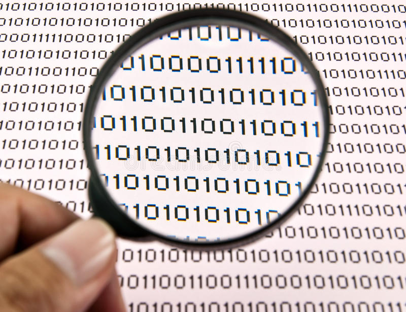 Magnifying glass and binary code. Hand holding magnifying glass to see binary code royalty free stock photos