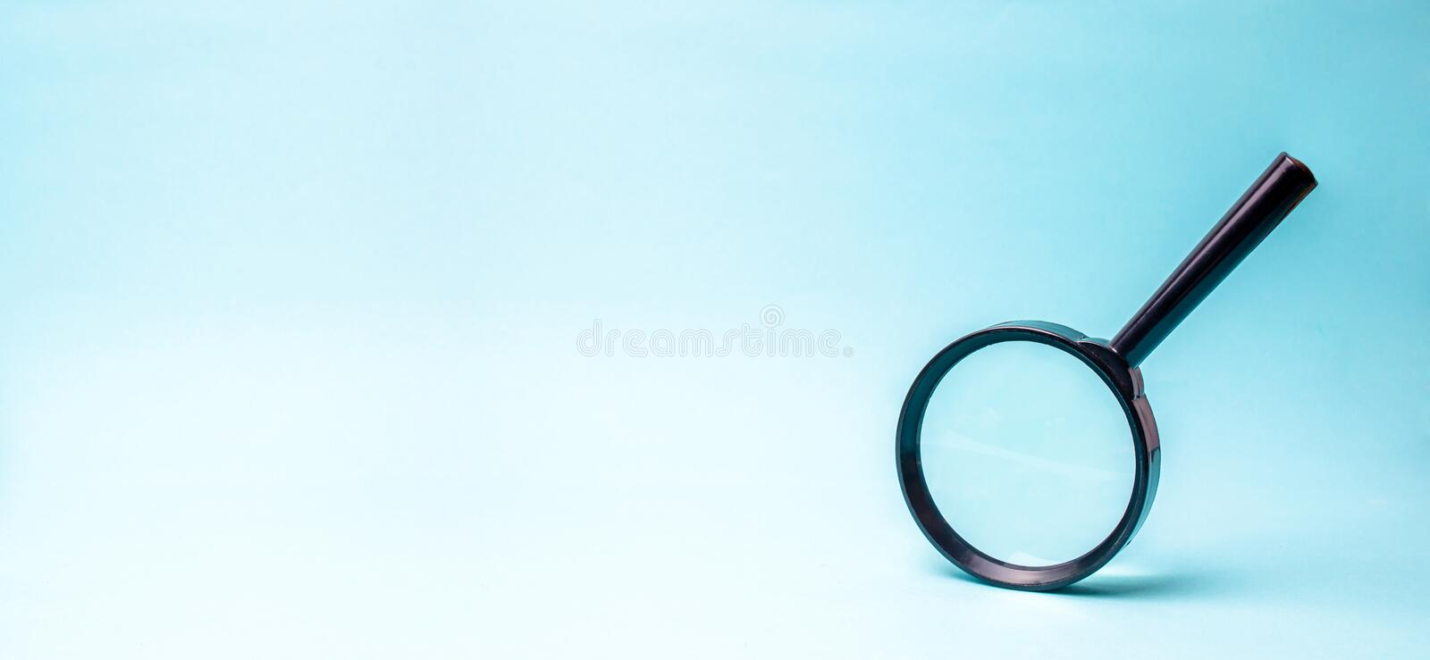 Magnifying glass on blue background. search and analysis, analytics and study of details. Validation, identification of fakes royalty free stock image