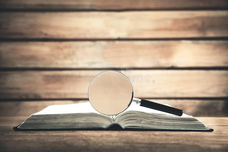 Magnifying glass with book on wooden table. Search and discover royalty free stock image