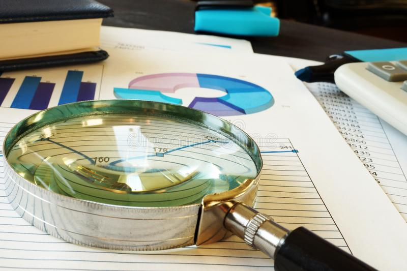 Magnifying glass on business documents. Accounting and financial audit. Magnifying glass on the business documents. Accounting and financial audit royalty free stock photo