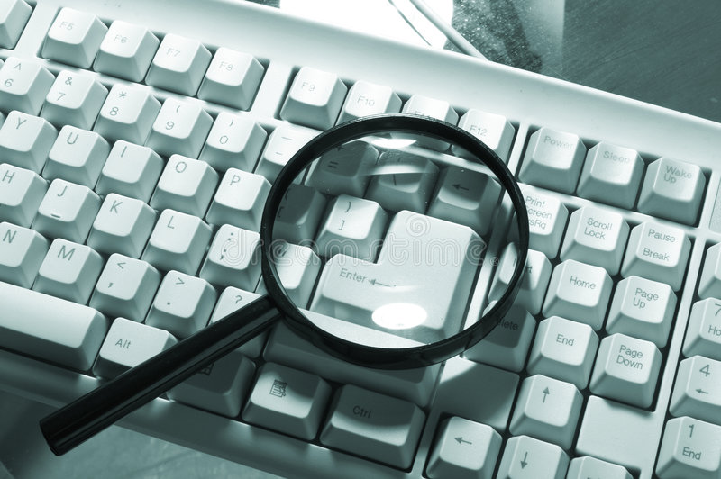 Magnifying glass, button, key. On the table stock photo