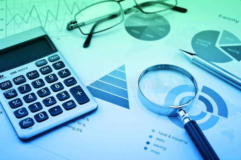 Magnifying glass, calculator, pen, and glasses on business budget graph, blue and green tone, Financial success concept royalty free stock photos