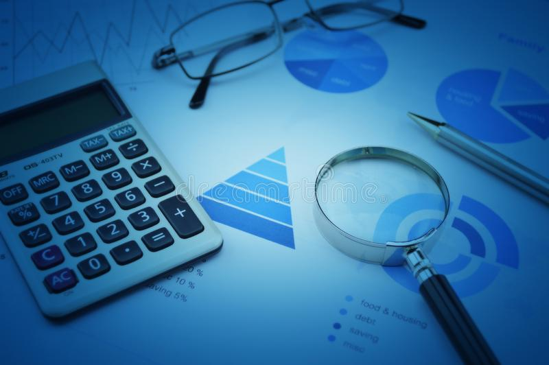 Magnifying glass, calculator, pen, and glasses on business budget graph, Financial research concept stock photography