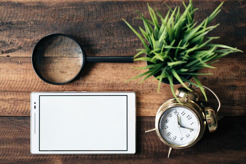 Magnifying glass, clock, green plant and digital tablet with blank screen on wooden table background royalty free stock photo