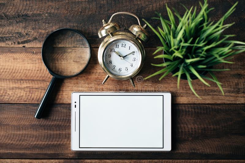 Magnifying glass, clock, green plant and digital tablet with blank screen on wooden table background royalty free stock image