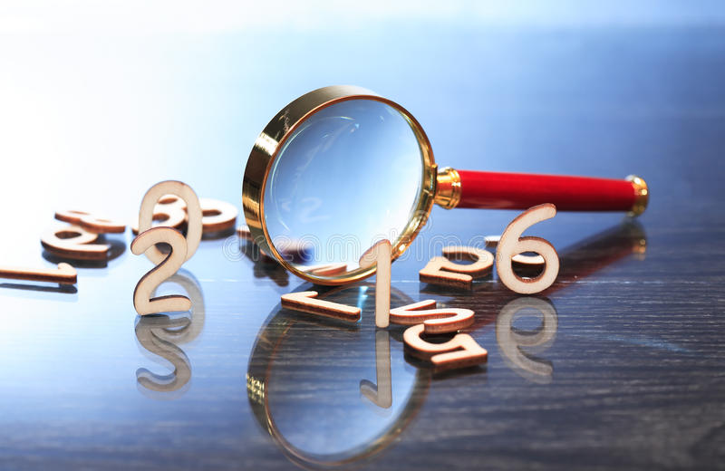 Magnifying Glass And Digits. Investigation concept. Magnifying glass near set of wooden digits stock image