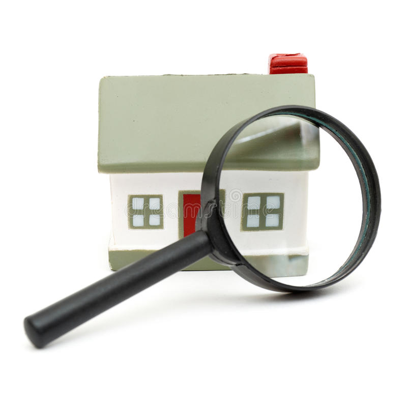 A magnifying glass examining model home. Isolated on white royalty free stock photos