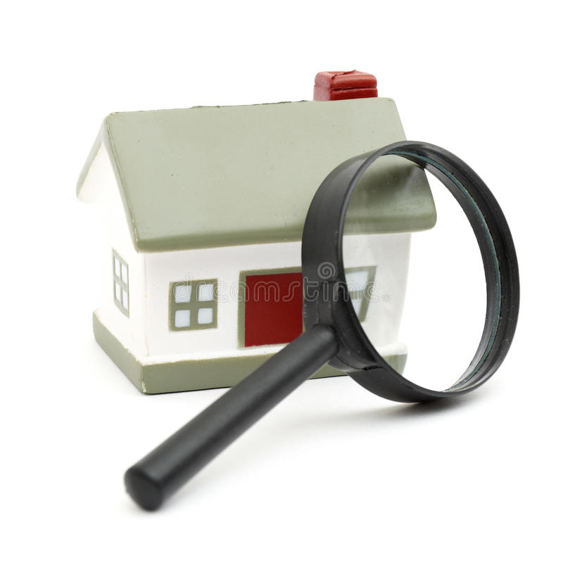 Magnifying glass examining model home. Isolated on white stock photo